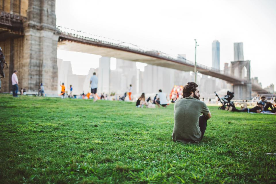 guy man people grass field bridge architecture New York city urban NYC buildings lifestyle group