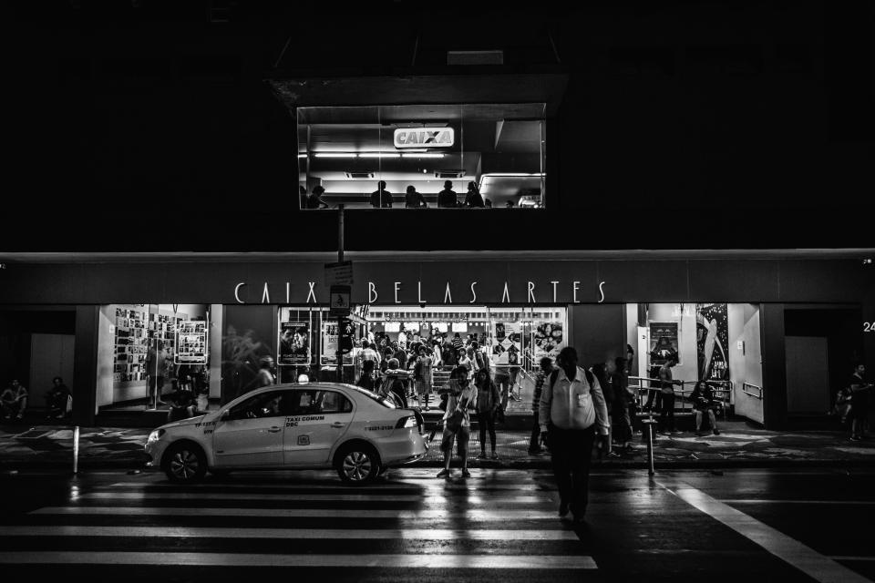 urban city establishment building structure infrastructure store shop black and white monochrome people pedestrian taxi car vehicle transportation