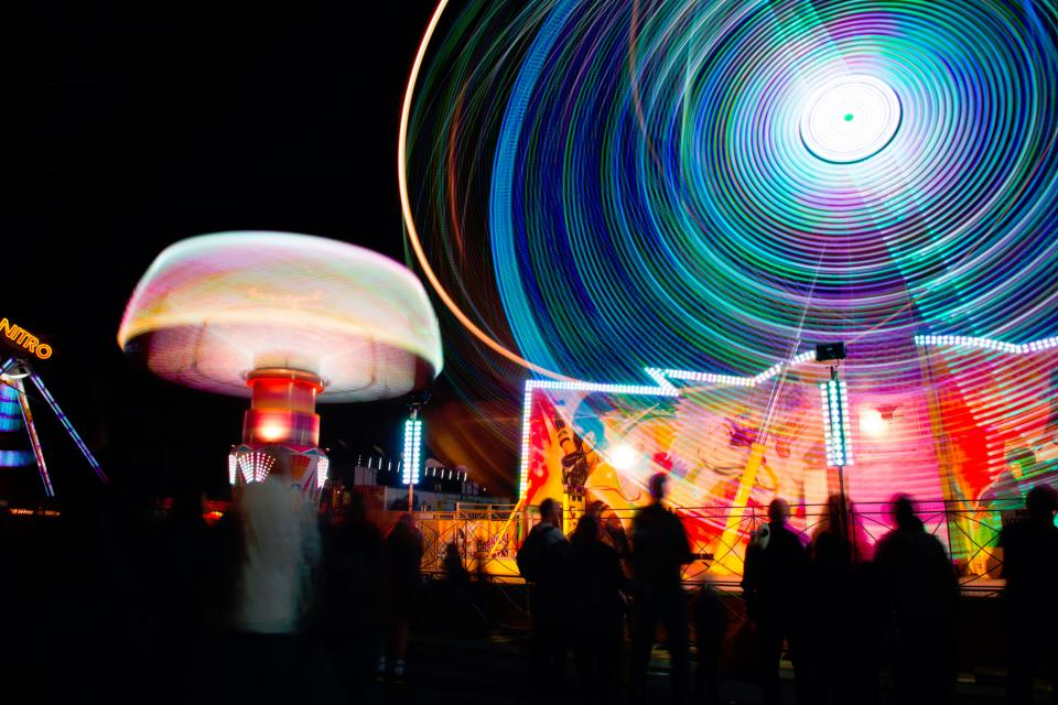 fun carnival lights ferris wheel round motion long exposure people crowd