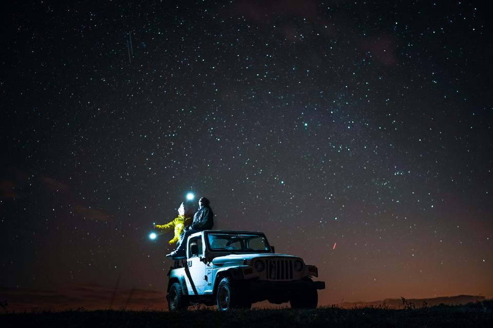 dark night stars sky flashlight light people man woman travel car vehicle landscape mountain nature