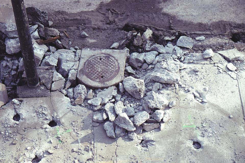 construction street sidewalk rocks stones concrete sewer manhole post