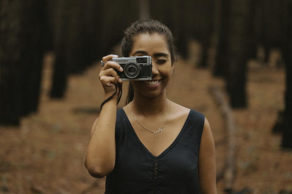 camera film woman smile photographer accessories bun nature woods forest