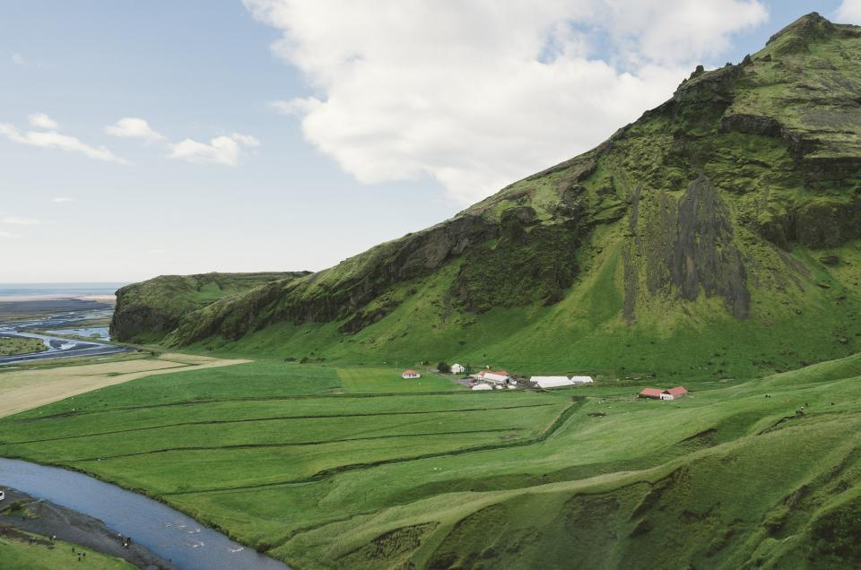iceland green grass fields valleys country farm nature mountains valleys water stream lake hills