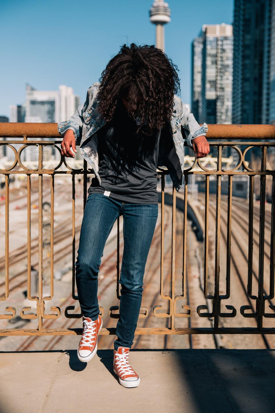 people man guy curly hair red sneakers sunny day daylight bridge architecture buildings city urban skyline steel metal railway track outdoors