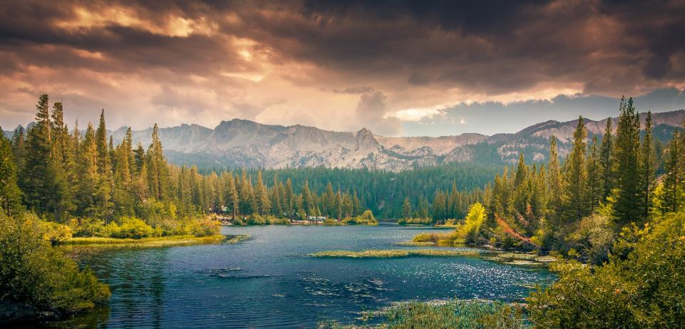 sky clouds mountains hills trees lake water nature rocks grass