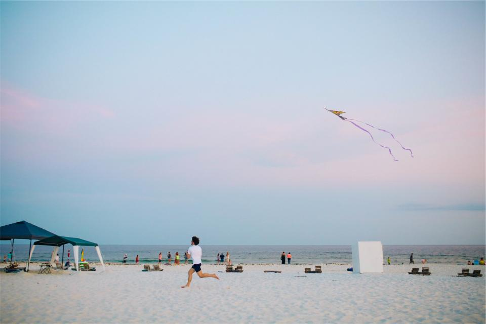 kite beach sand shore people running guy sky ocean water