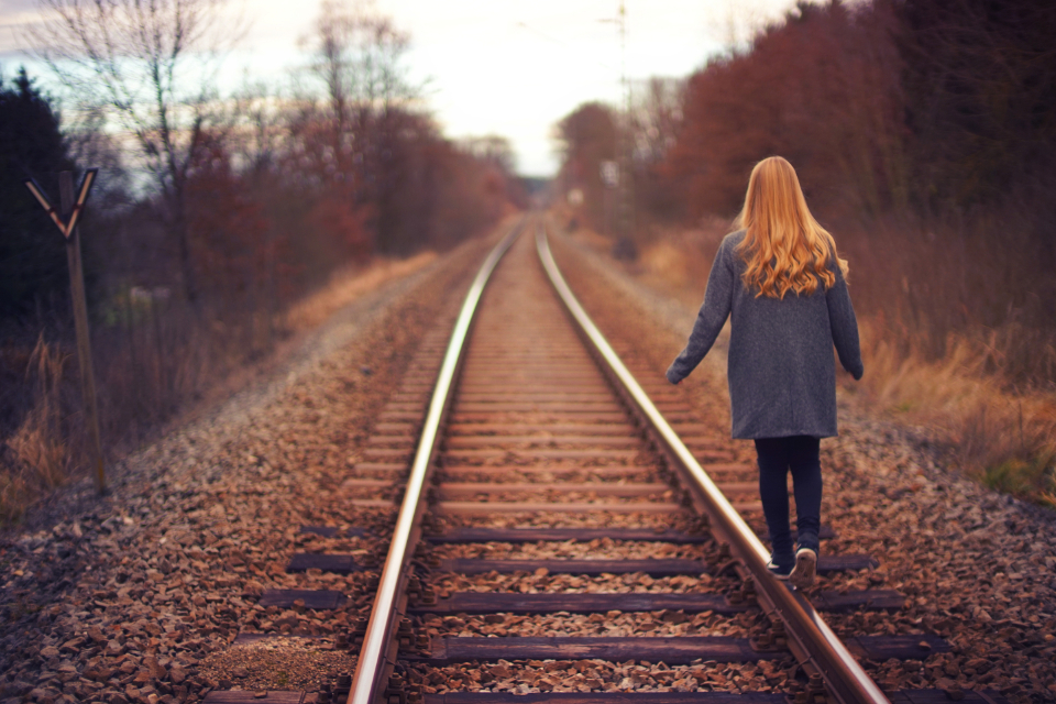 young girl tracks railway train alone lonely balance red hair female people child autumn walk
