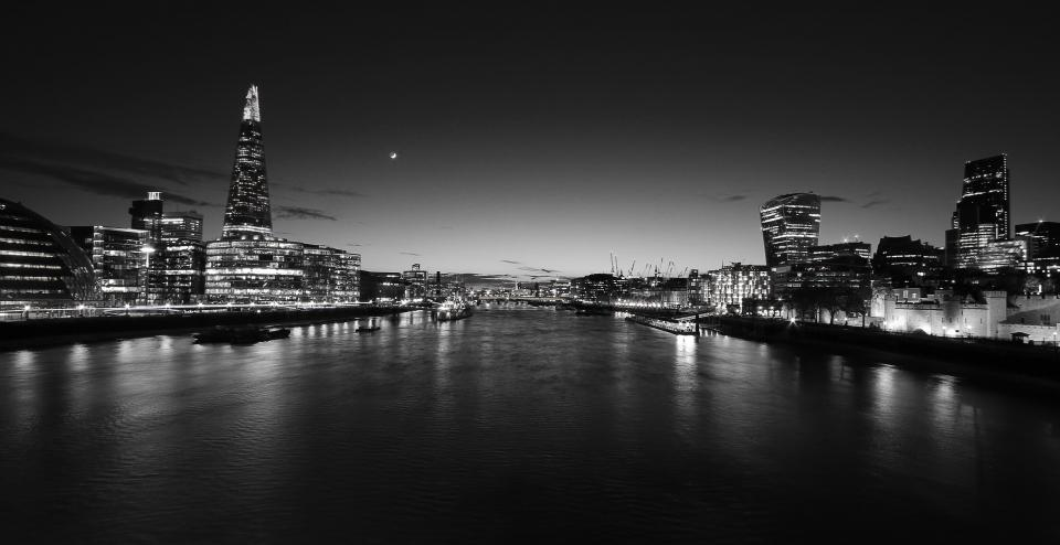architecture buildings city office residential high rise skyscrapers infrastructures water river ports docks boats reflection sky clouds night stars lights urban metro black and white