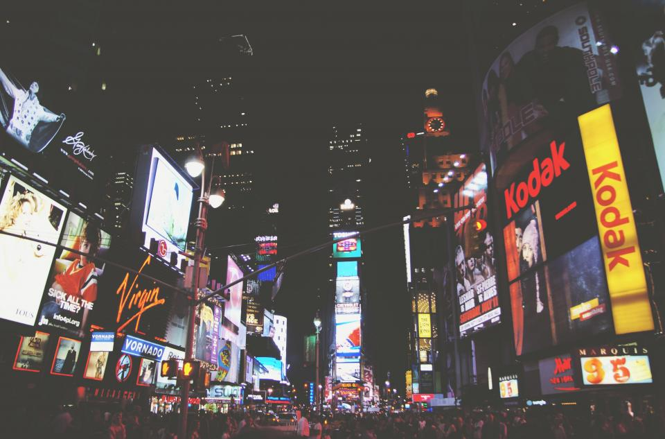 night dark crowd people party new york city buildings towers times square busy lights signs ads billboards evening