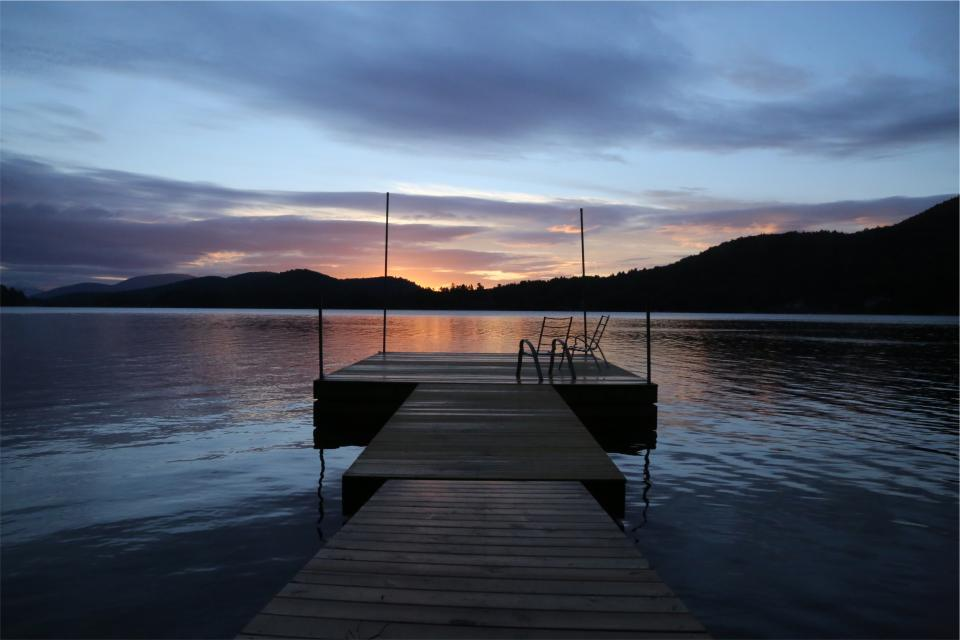 sunset lake water dock cottage mountains dusk sky clouds