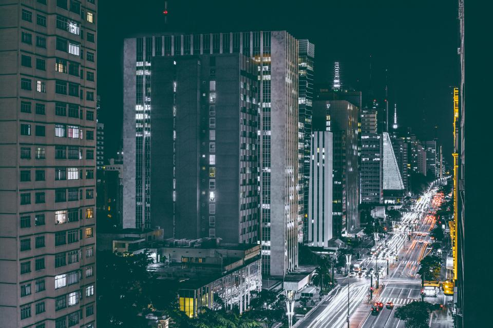 city urban buildings architecture cityscape high rises towers apartments condos cars streets road traffic lights dark night evening