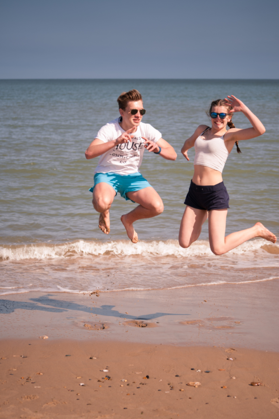 people jumping beach boy girl fun play ocean water sea shore coast sand vacation happy young leisure summer