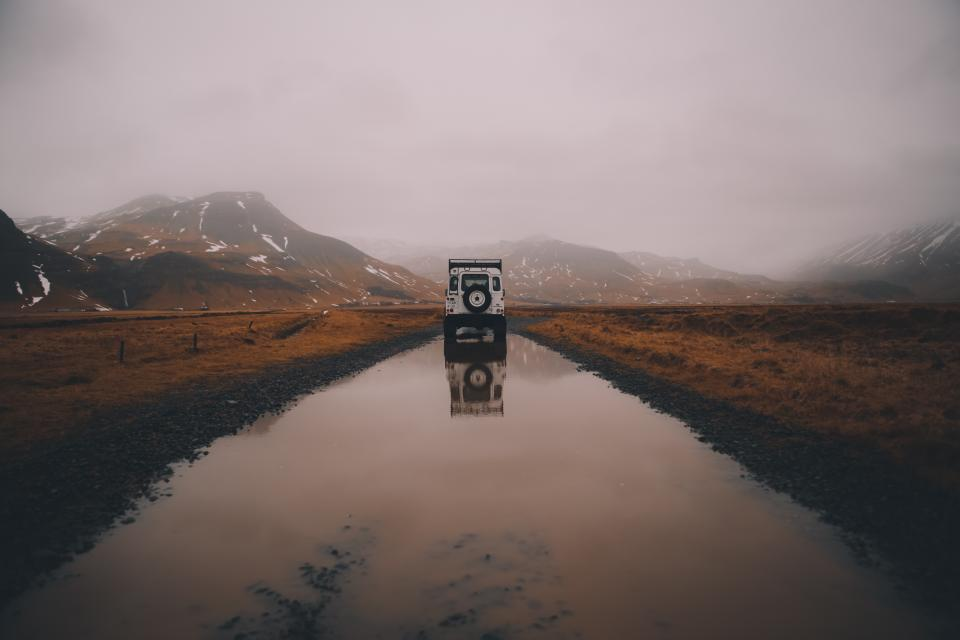 road vehicle mountains reflect clouds grass fog field travel trip sky jeep reflection snow water trees fence