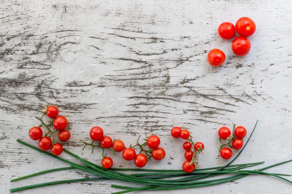 red tomato fruit vegetable food green leaf wooden table