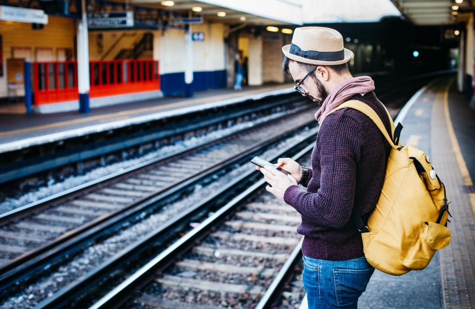 people man bag cap hat clothing waiting texting phone travel track railway train station building