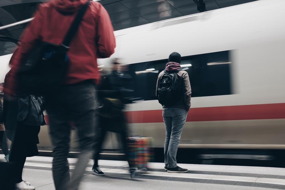 people men waiting passengers travel train station transportation blur