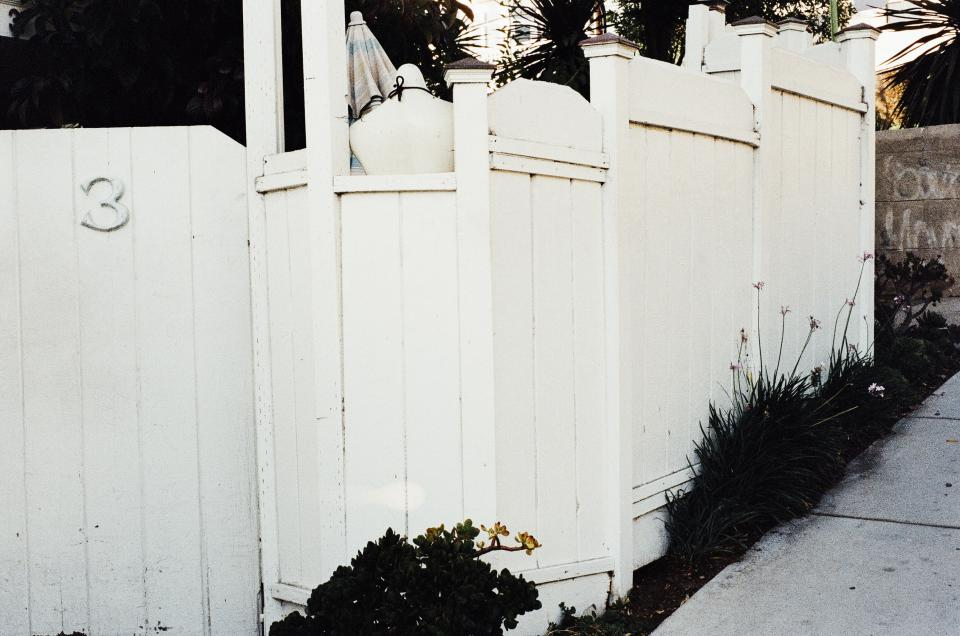 white gate fence sidewalk house