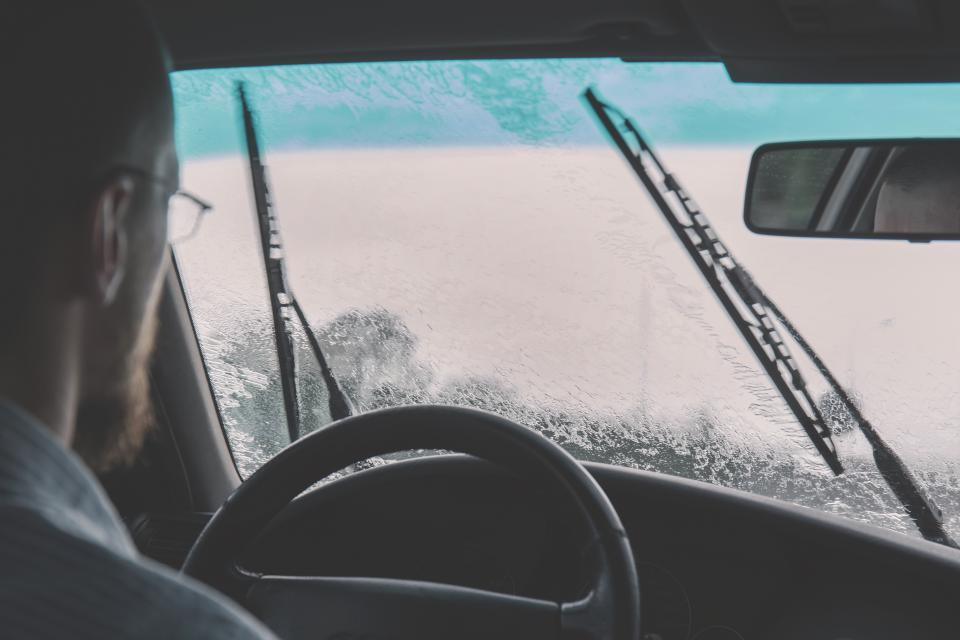 car windshield driving raining windshield wipers guy man people steering wheel automotive