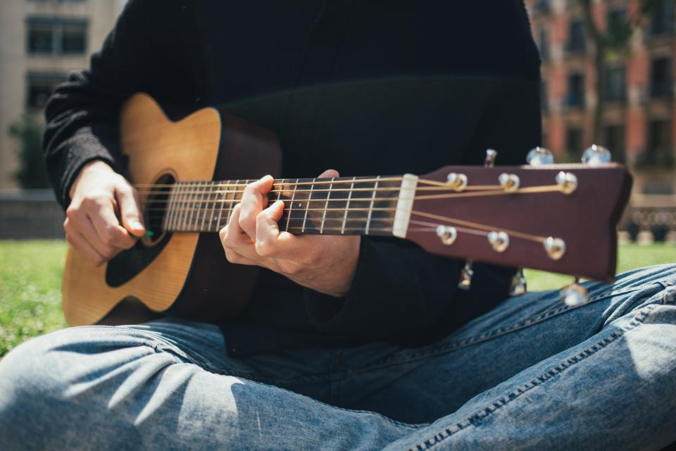 people playing guitar music sounds strings chords musician guitarist musical instrument playground green grass outdoors