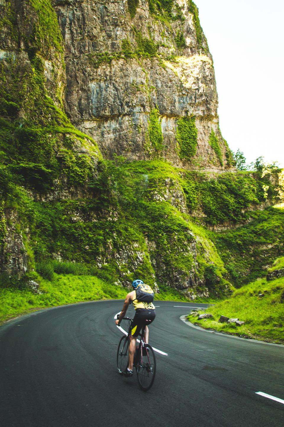 cyclist bike bicycle racing road street pavement fitness exercise guy man people backpack mountains cliffs green grass sports