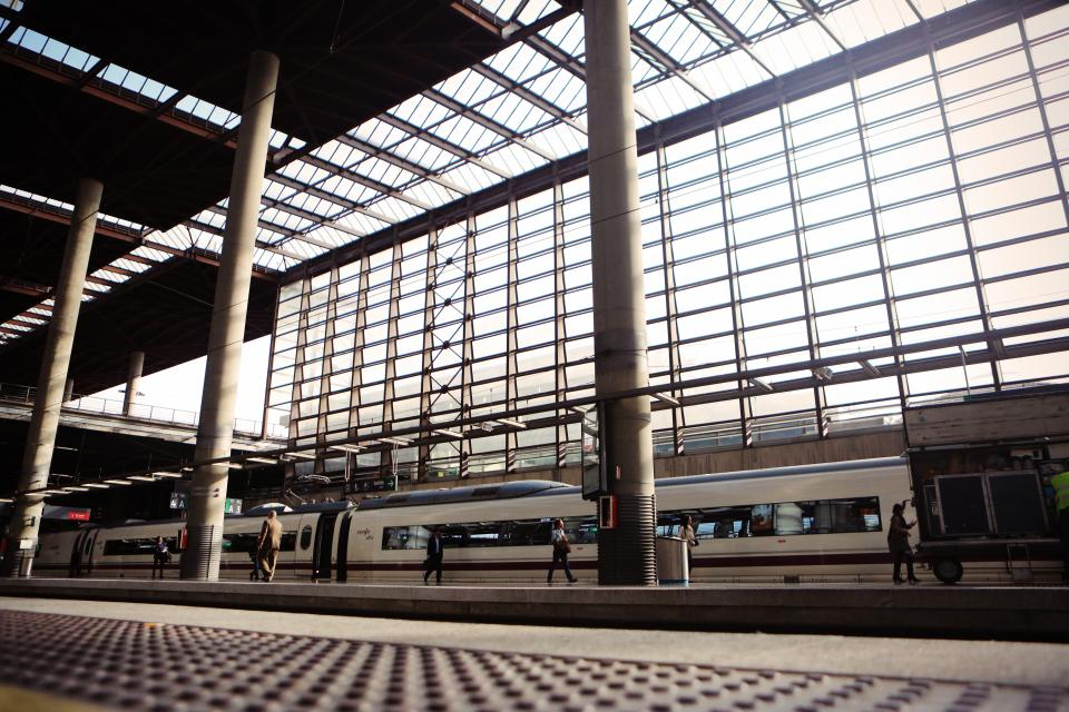 train station tracks transportation travel passenger walking pedestrian beams pillars windows sunlight