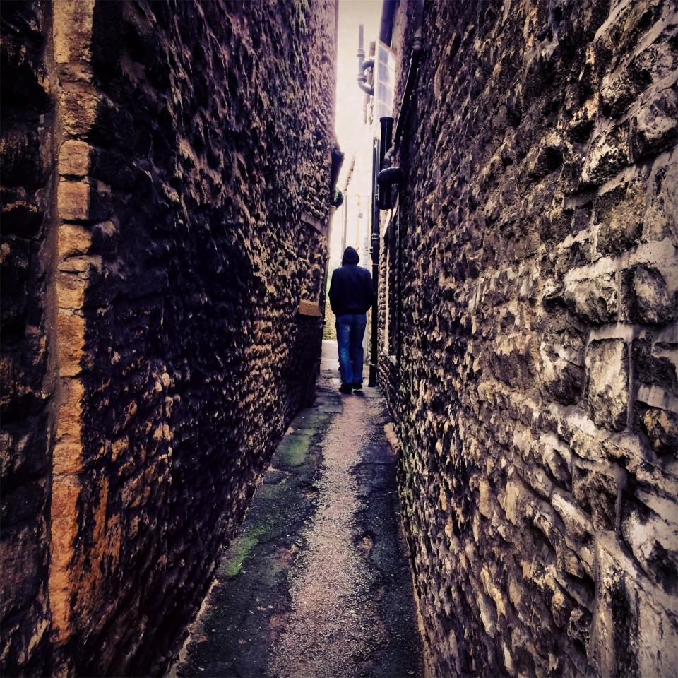 alley stones walls pavement guy man hoodie people