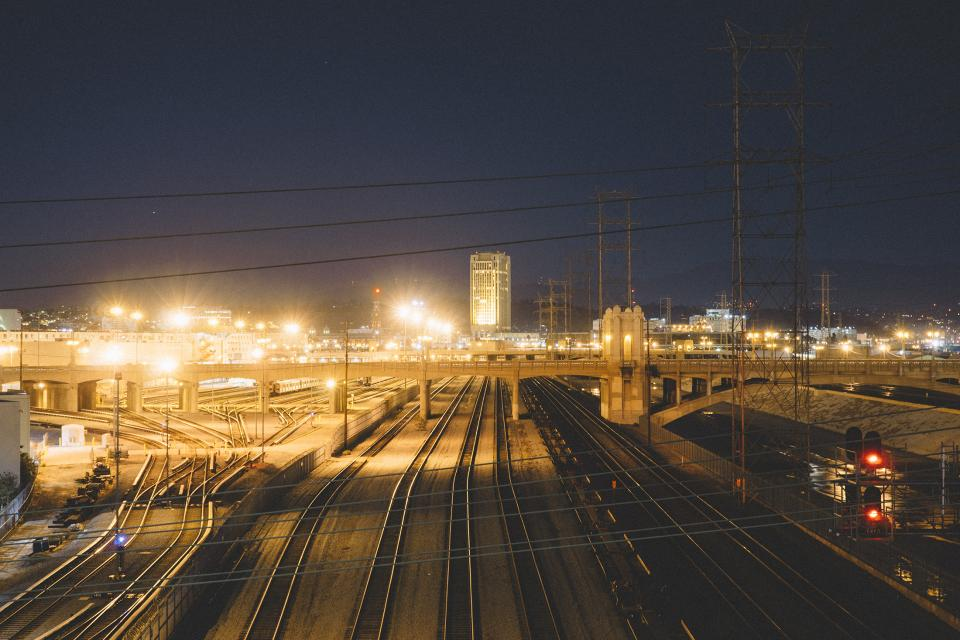 train tracks railroad railway city dark night lights buildings bridge power lines evening