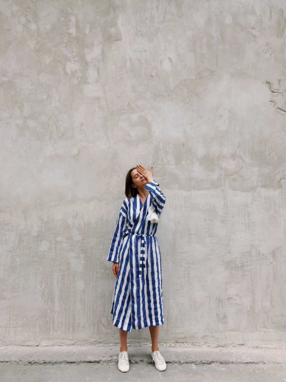 woman cover face hand stripes dress girl female people white shoes concrete wall minimal street