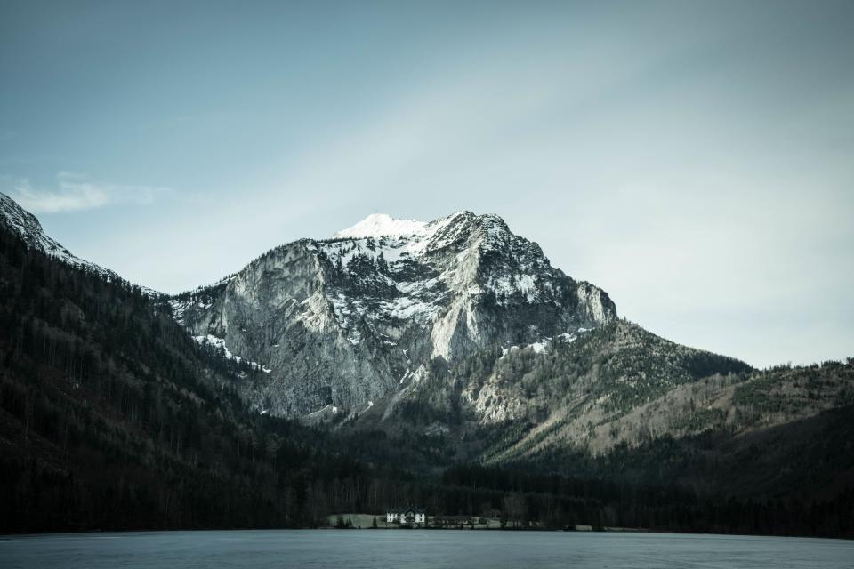 blue sky mountain peak cliffs snow cold water lake trees house shadow
