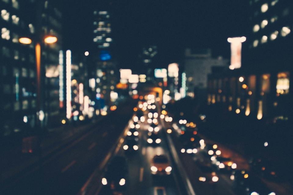 blurry lights cars traffic roads street buildings city dark night evening