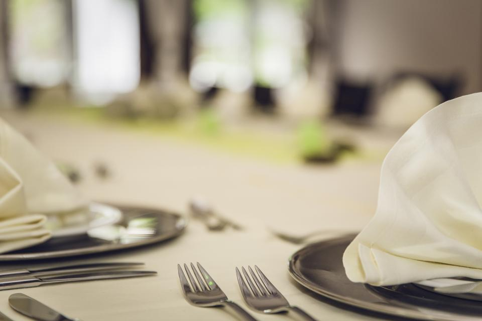 still items things table setting silverware forks knives plates napkins spread bokeh