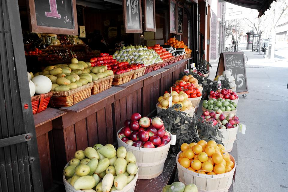 fruits vegetables street market pears apples oranges mangos tomatoes cantaloupe baskets prices