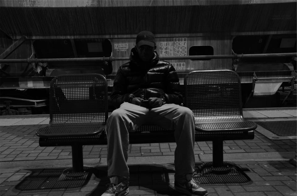 young guy man sitting hat jacket pants chairs black and white people