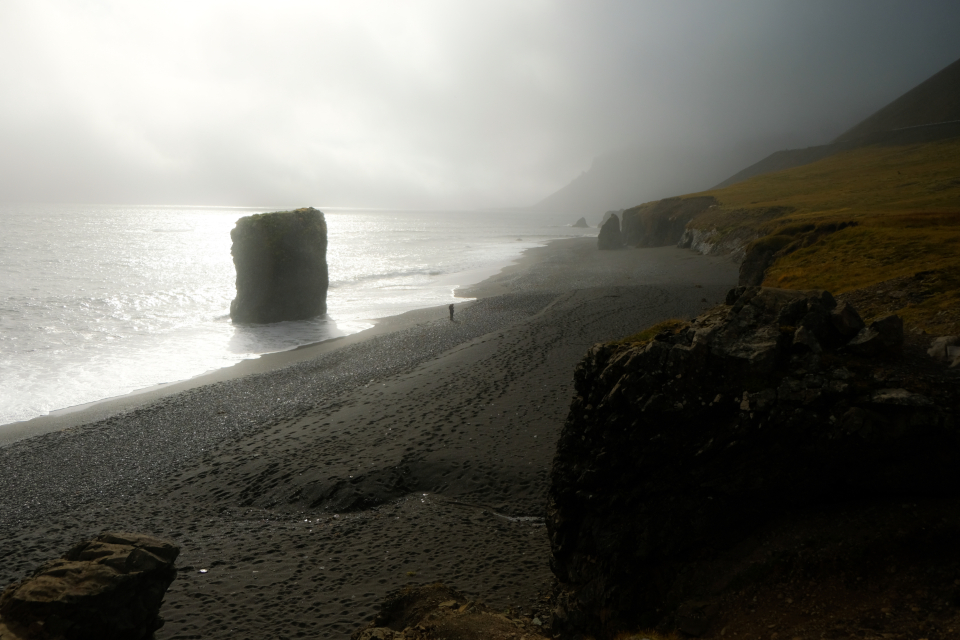 iceland beach fog moody gloomy nature landscape outdoors shore ocean water sea rocks person walking majestic tourism travel explore wanderlust clouds climate environment weather misty