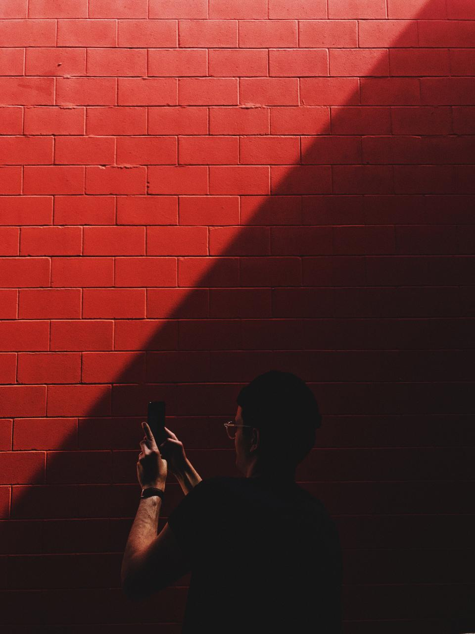 red wall sunlight dark people man guy mobile phone camera photography