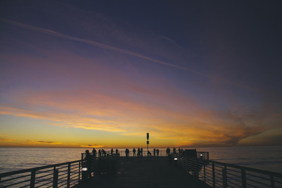 purple yellow sky sunset dock pier people ocean water dark dusk clouds railing beach