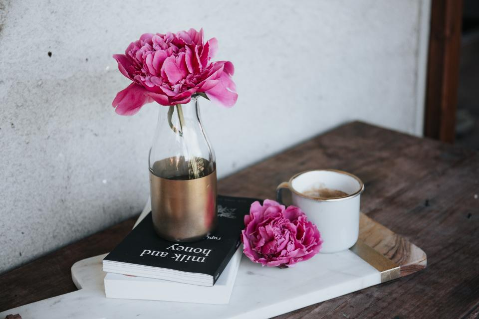pink flower vase display table books coffee drink