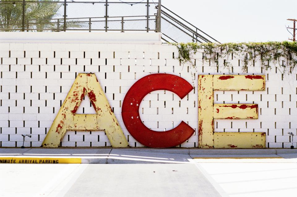 ace letters concrete wall vines white red sidewalk street fence