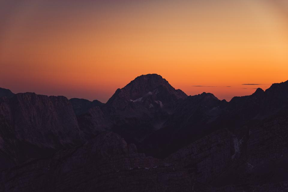 mountains peaks cliffs sunset dusk orange sky shadows landscape nature adventure