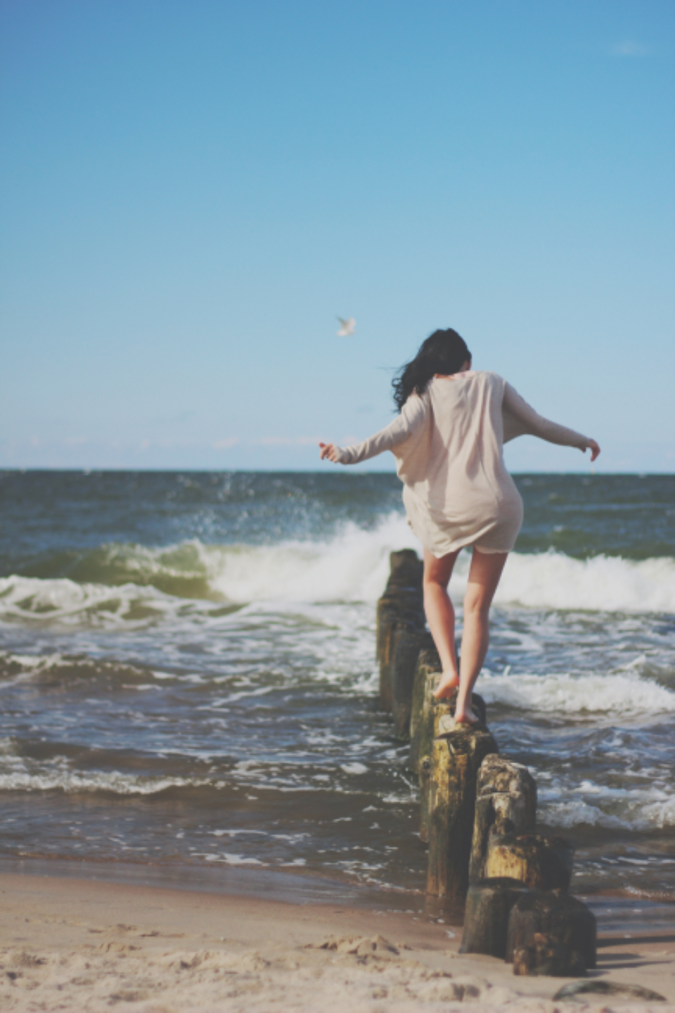woman stepping ocean sea water wind blue sky beach summer girl female legs