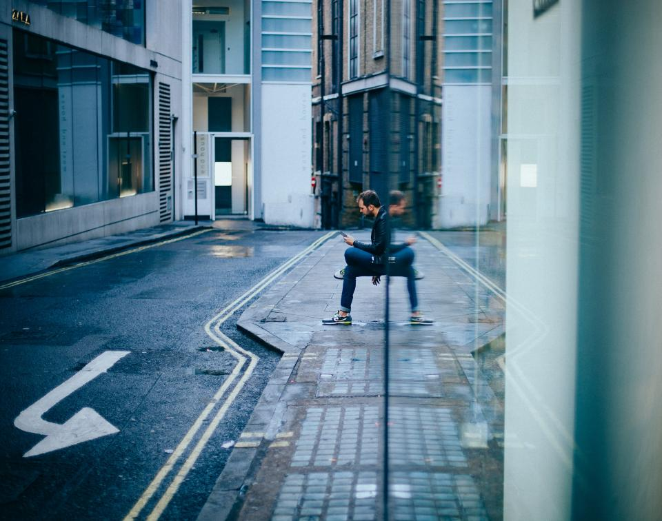 building architecture road street sidewalk people guy man sitting waiting texting wall reflection