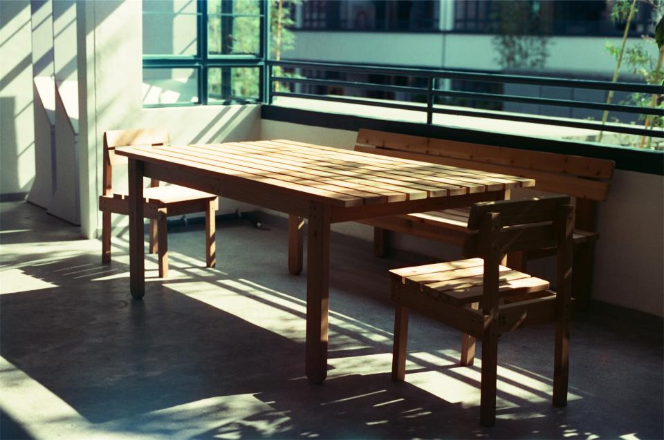 wood table chairs bench sunlight balcony