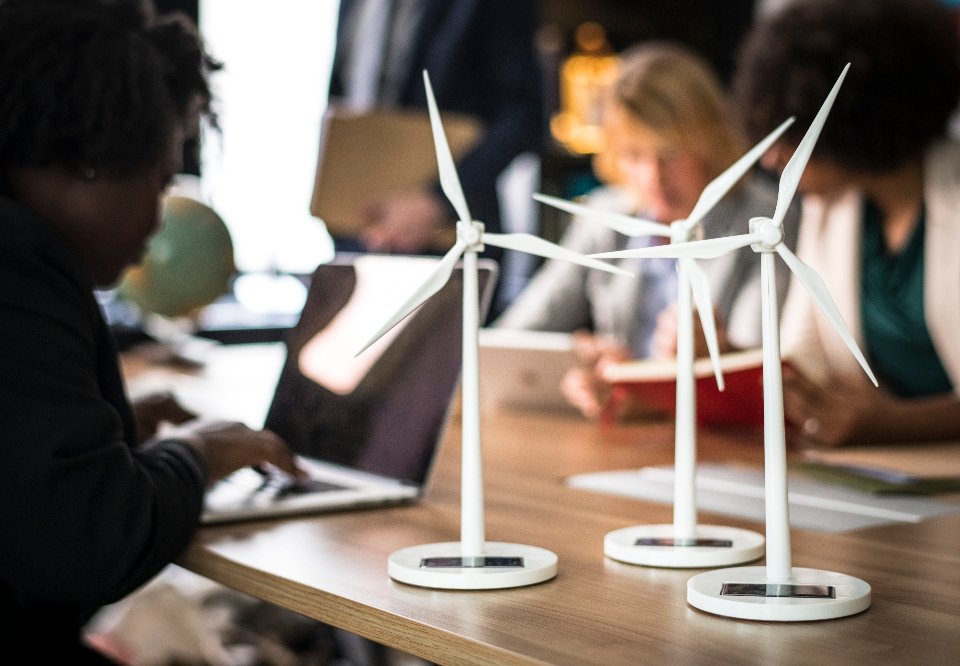alternative energy blur business people businessman businesswoman climate change computer device discussing ecology environment environment friendly fan global warming innovation laptop meeting meeting table model name presentation profe