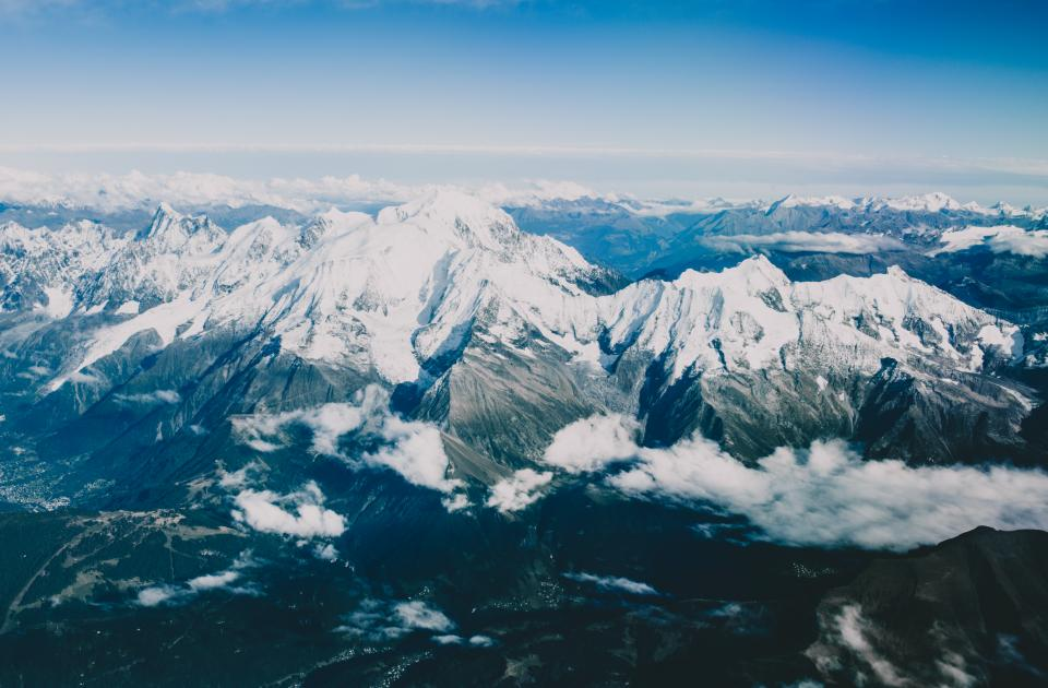 mountains peaks summit snow cliffs landscape clouds blue sky aerial view nature outdoors adventure hiking