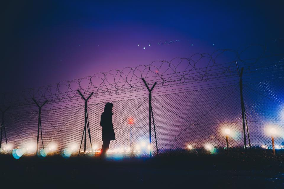 dark night sky lights wire fence people man alone silhouette