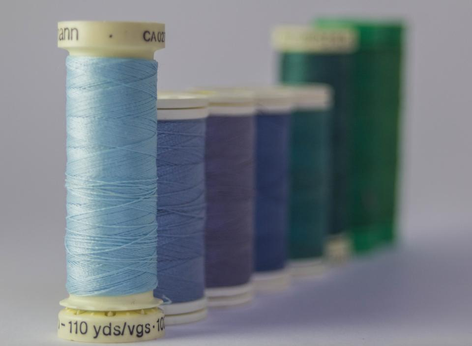 threads colors row queue sewing materials pastel blue green bokeh still