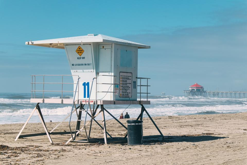 lifeguard beach coast sand water people couple man woman lovers trash can wave number sky clouds lifeguard post eleven