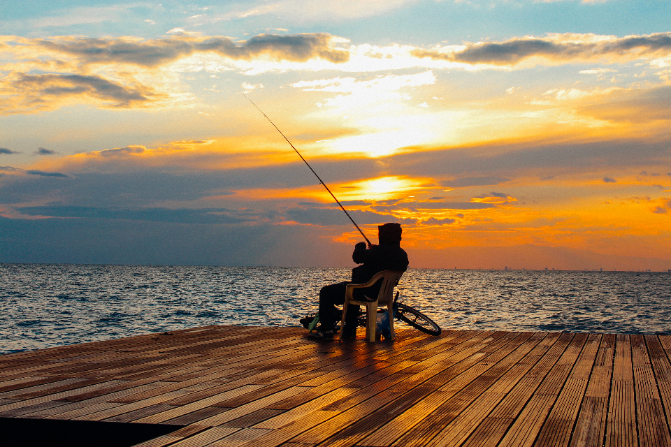 man fishing sunset travel landscape view sun sea water ocean river lake wood dock pier jetty seat