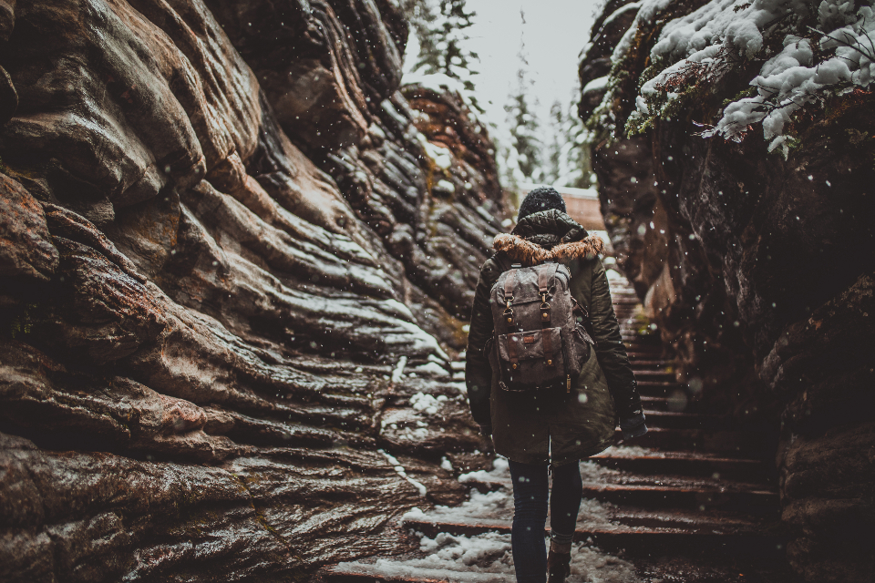 girl backpack photographer walking hiking walk hike travel explore travelling exploring adventure adventuring winter cold snow snowing cave