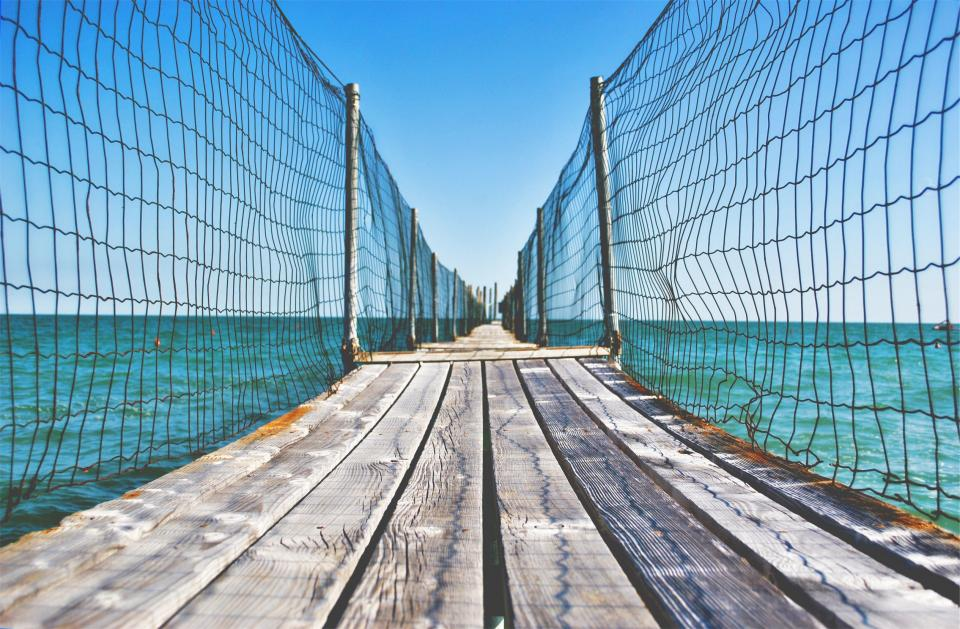 wood bridge planks path fence water ocean sea blue sky